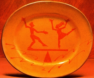 Orange plate showing Man and Woman dancing on a seesaw